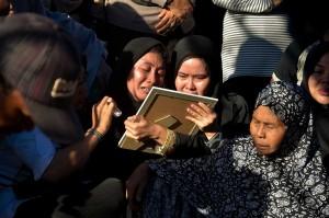 Anggota keluarga Iptu Anumerta Auzar yang menjadi korban penyerangan Mapolda Riau menangis saat pemakaman almarhum. AFP/Wahyudi