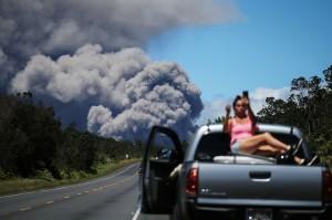 Sambil bersantai, seorang warga mengabadikan letusan gunung.