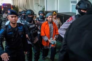 Aman Abdurrahman mendapat pengawalan ketat saat akan menjalani sidang dengan agenda tuntutan terhadap dirinya. AFP/Bay Ismoyo