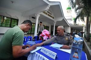 Petugas kepolisian melayani warga yang memperpanjang masa berlaku SIM-nya di halaman Masjid Hikmatul Ilmi, Kramat Jati, Jakarta Timur, Jumat, 1 Juni 2018.