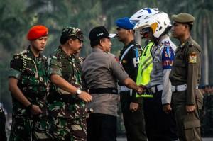 Kapolri Jenderal Tito Karnavian (tengah) disaksikan Panglima TNI Marsekal Hadi Tjahjanto (kedua kiri) berjabat tangan dengan perwakilan pasukan gabungan seusai menyematkan tanda operasi dalam apel gelar pasukan Operasi Kepolisian Terpusat Ketupat 2018 di Monas, Jakarta, Rabu, 6 Juni 2018.