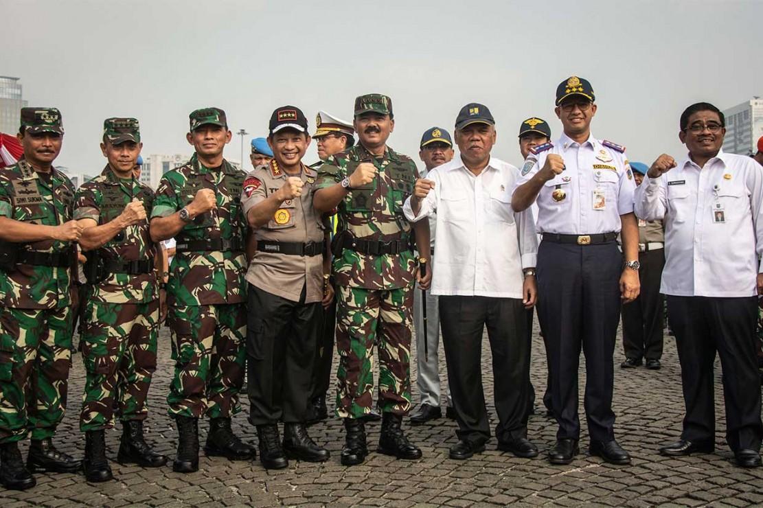 Kapolri Jenderal Tito Karnavian (keempat kiri), Panglima TNI Marsekal Hadi Tjahjanto (keempat kanan), Menteri PUPR Basuki Hadimuljono (ketiga kanan), KSAU Marsekal Yuyu Sutisna (ketiga kiri), Gubernur DKI Jakarta Anies Baswedan (kedua kanan), KSAD Jenderal Mulyono (kedua kiri), Plt Gubernur Sulawesi Selatan Soni Sumarsono (kanan), dan KSAL Laksamana Siwi Sukma Adji (kiri) berfoto bersama seusai mengikuti apel gelar pasukan Operasi Ketupat 2018 di Monas, Jakarta.