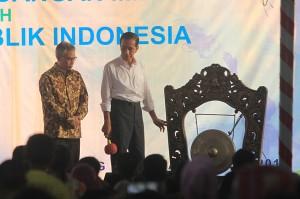 Presiden Joko Widodo (kanan) memukul gong disaksikan Ketua Dewan Komisioner OJK Wimboh Santoso (kiri) saat peluncuran pembiayaan lembaga keuangan mikro untuk nelayan di Karangsong, Indramayu, Jawa Barat.