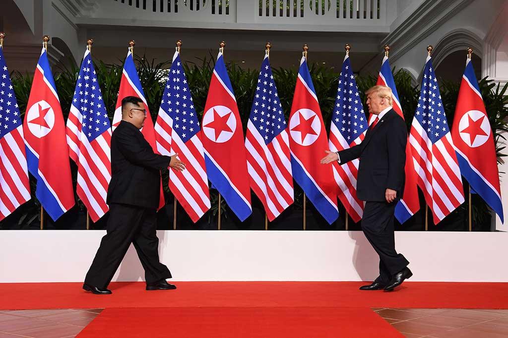 Presiden AS Donald Trump dan pemimpin Korea Utara Kim Jong Un bertemu untuk pertema kalinya di Hotel Capella, Singapura, Selasa, 12 Juni 2018. Dengan latar belakang bendera kedua negara, keduanya kemudian berjabat tangan.