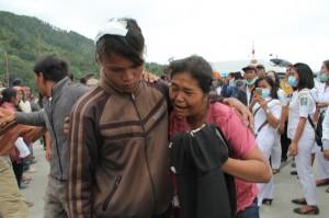 Penumpang KM Sinar Bangun yang selamat dan sempat mendapatkan perawatan (kiri) dibantu anggota keluarganya saat tiba di posko Pelabuhan Tigaras, Danau Toba, Simalungun, Sumatra Utara.