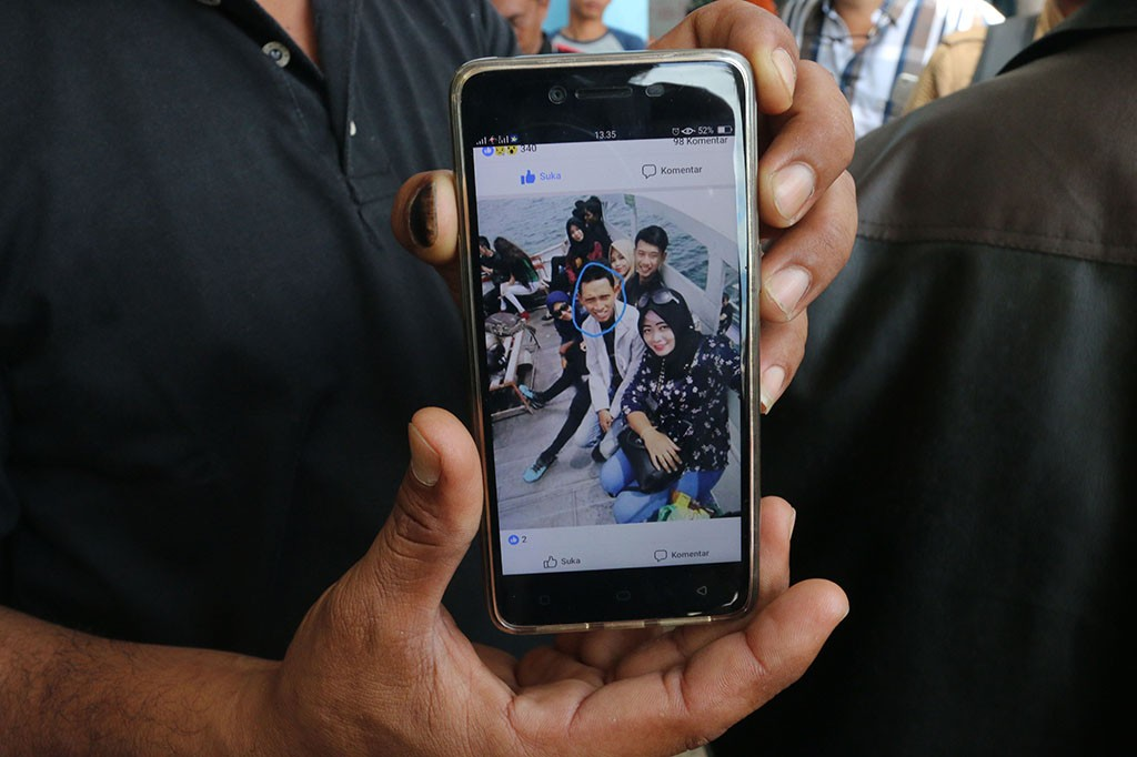Keluarga korban kapal tenggelam KM Sinar Bangun menunjukkan foto anggota keluarganya yang merupakan penumpang hilang bernama Sarsubhan alias Yusuf (kedua kanan), di posko Pelabuhan Tigaras, Simalungun, Sumatera Utara.