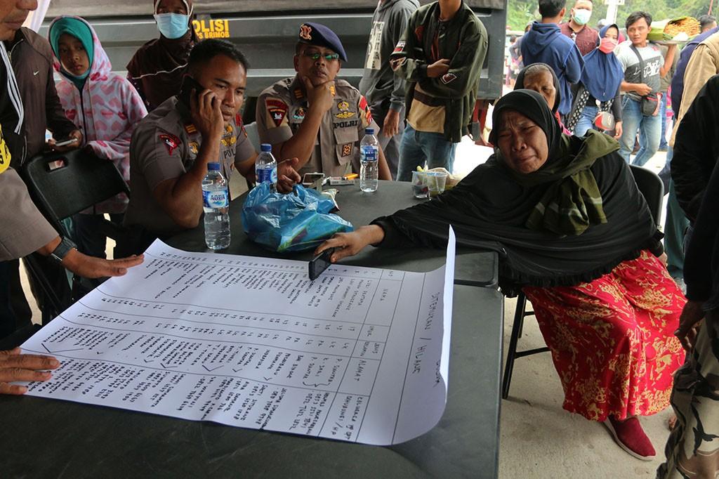 Anggota keluarga penumpang KM Sinar Bangun menangis sambil melihat daftar nama penumpang yang hilang, di posko Pelabuhan Tigaras, Danau Toba, Simalungun, Sumatra Utara.