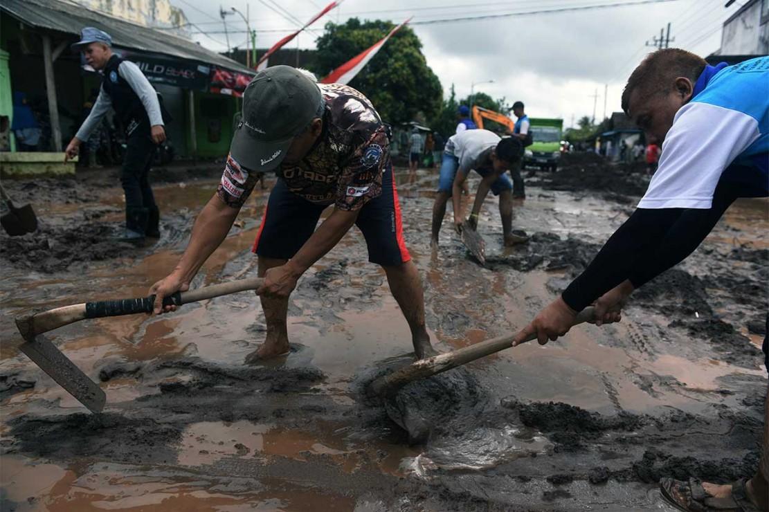 Relawan bergotong-royong membersihkan endapan lumpur di lokasi dampak banjir bandang di Desa Alas Malang, Singojuruh.