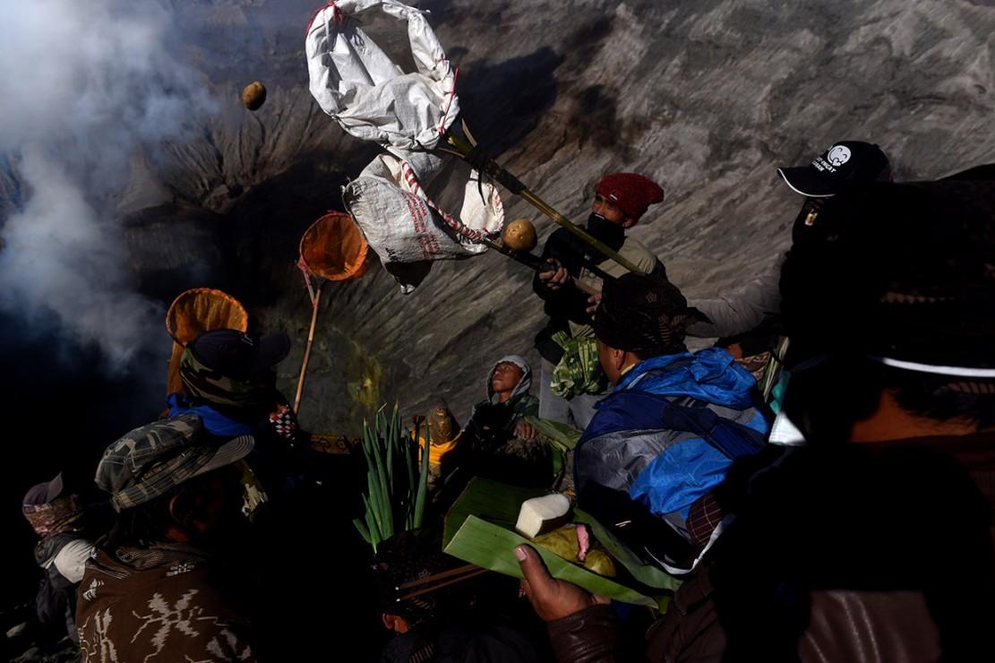 Warga berebut uang sesaji yang dilarung masyarakat Suku Tengger ke kawah Gunung Bromo pada Upacara Yadnya Kasada.