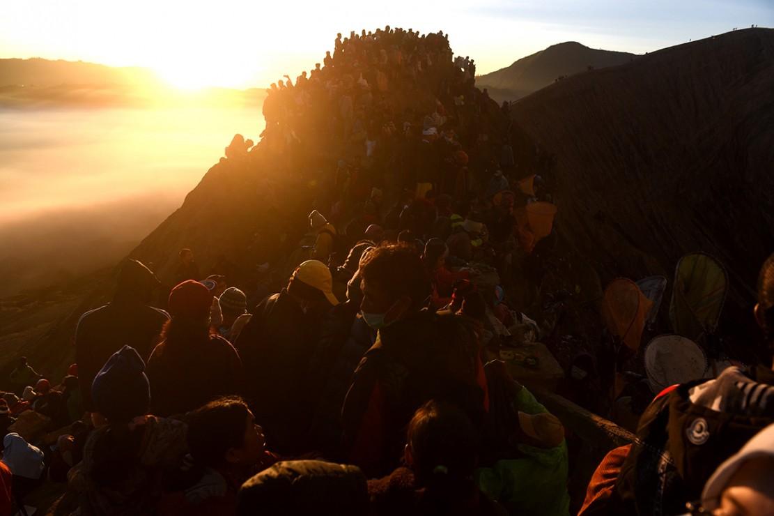 Wisatawan dan masyarakat suku Tengger mengikuti Upacara Yadnya Kasada di bibir kawah Gunung Bromo, Probolinggo, Jawa Timur.