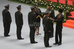Presiden Joko Widodo (kanan) memberikan penghargaan Bintang Bhayangkara Nararya kepada empat personil polisi berprestasi pada peringatan HUT ke-72 Bhayangkara, di Istora Senayan, Jakarta.