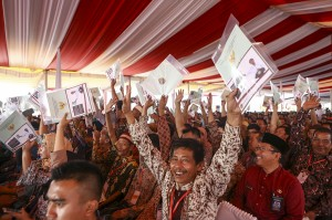 Warga menunjukkan sertifikat tanah saat mengikuti penyerahan sertifikat hak atas lahan tanah oleh Presiden Joko Widodo di pelataran Benteng Kuto Besak (BKB), Palembang, Sumatera Selatan.