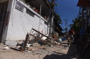 Warga bersepada di samping bangunan yang rusak akibat gempa bumi di Gili Trawangan, Lombok Utara, NTB.