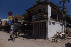 Tampak banyak bangunan toko, restoran, penginapan, dan rumah yang rusak berat.