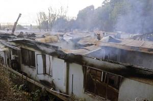 Asap mengepul dari puing-puing yang tersisa setelah kebakaran terjadi di panti jompo di komune Chiguayante, Concepcion, Chile, Selasa, 14 Agustus 2018 waktu setempat.