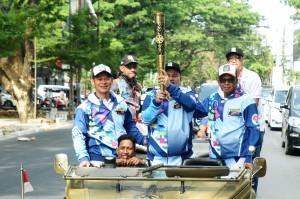 Gubernur Sulsel Nurdin Abdullah (kanan) bersama Ketua Panitia Pelaksana Asian Para Games (Inapgoc) Raja Sapta Oktohari (kiri) dan atlet lempar lembing Bahar Rahman (tengah) membawa obor saat Pawai Obor Asian Para Games di Makassar, Sulawesi Selatan.