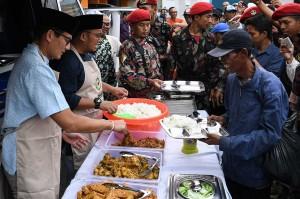 Bakal calon wapres Sandiaga Uno (kiri) bersama Ketua Umum PP Pemuda Muhammadiyah Dahnil Anzar Simanjuntak (kedua kiri) melayani makan gratis untuk kaum duafa di Gedung PP Muhammadiyah, Menteng, Jakarta Pusat, Jumat, 14 September 2018.