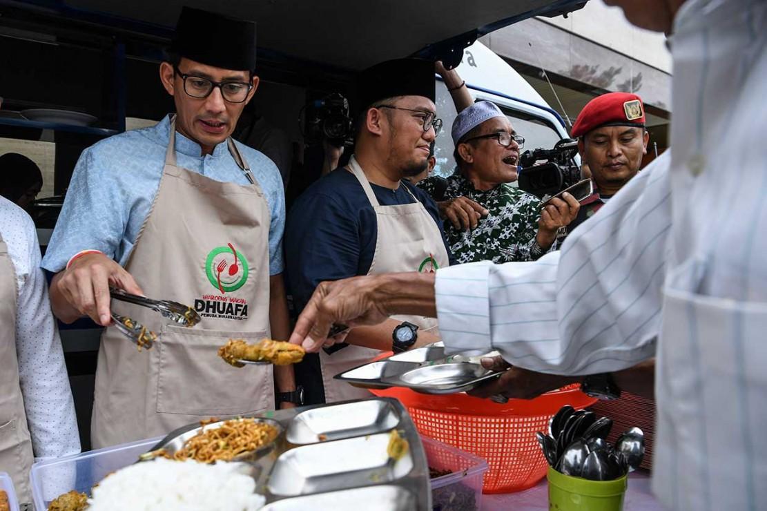 Sandiaga melayani warga dengan memberikan menu berupa mie dan ayam goreng langsung ke piring-piring warga yang berbaris di dekat mobil warung duafa, di halaman Gedung PP Muhammadiyah.