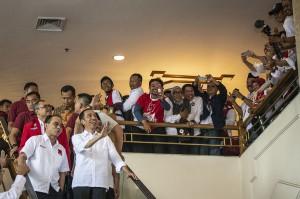 Presiden Joko Widodo (kedua kiri) bersama Ketua Umum DPP Projo Budi Arie Setiadi (kiri) menyapa relawan ketika menghadiri Rakernas IV Projo di Jakarta. Jokowi hadir untuk memberikan pengarahan khusus kepada para relawan.