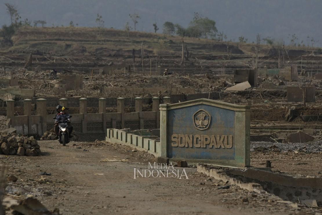 Warga melintas diantara puing sisa bangunan sekolah yang dulunya merupakan wilayah Desa Cipaku, Kecamatan Darmaraja, Kabupaten Sumedang, Jawa Barat.