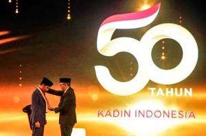 Presiden Joko Widodo (kiri) menerima penghargaan Tokoh Pemerataan Pembangunan Indonesia dari Ketua Umum Kadin Rosan P Roeslani pada acara HUT ke-50 Kadin, di Jakarta, Senin, 24 September 2018.