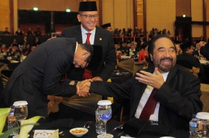 Cawapres nomor urut 02 Sandiaga Uno (kiri) berjabat tangan dengan Ketua Umum Partai NasDem Surya Paloh saat menghadiri HUT ke-50 Kadin.