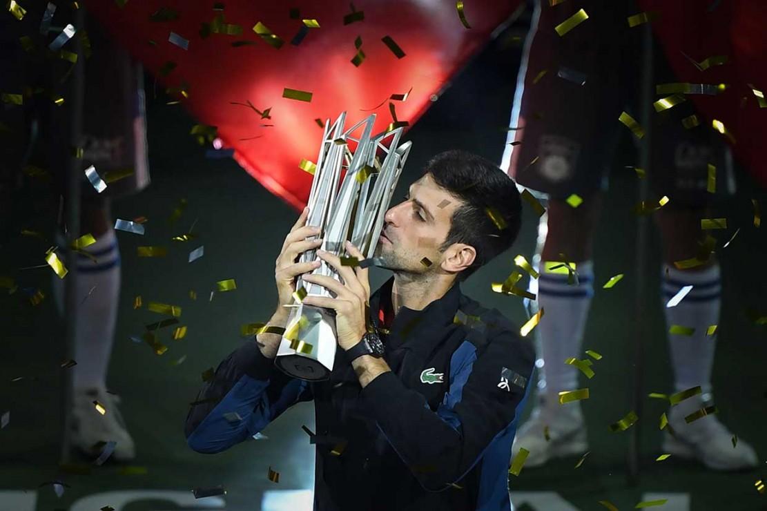 Petenis Serbia Novak Djokovic mencium trofi juara yang baru direbutnya di turnamen Shanghai Masters, Minggu, 14 Oktober 2018.