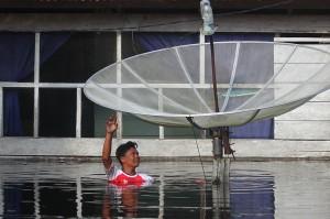 Seorang warga berusaha memindahkan antena parabola miliknya di daerah terdampak banjir di kelurahan Bukit Datuk, di Dumai, Riau.
