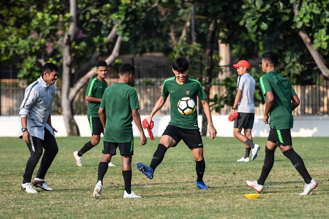 Pelatih Timnas Indonesia U-19 Indra Sjafri (kiri) memberikan arahan kepada sejumlah anak asuhnya saat menggelar latihan di Lapangan A Senayan, Jakarta, Sabtu, 20 Oktober 2018.