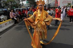 Warga Tionghoa mengenakan pakaian ulama Kong Hucu saat mengikuti kirab budaya dan ruwat bumi dengan menggotong joli atau tandu toapekong di sepanjang ruas Jalan Hayam Wuruk, Jakarta.