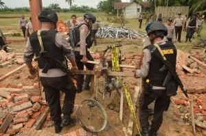 Petugas Satpol PP membantu personel kepolisian membersihkan puing bangunan dan kendaraan dinas yang dibakar oleh massa di Mapolsek Bendahara, Aceh Tamiang, Aceh, Rabu, 24 Oktober 2018.