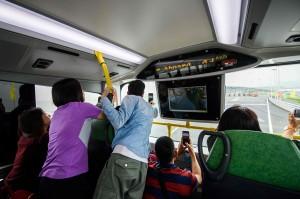 Para wisatawan mengabadikan gambar dari dalam bus yang membawanya menyusuri jembatan terpanjang di dunia.