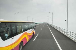 Bus wisata melaju menuju Hong Kong melewati jembatan Hong Kong-Macau-Zhuhai. Jembatan terpanjang di dunia yang menghubungkan Hong Kong-Macau dan Kota Zhuhai di daratan Tiongkok tersebut dibuka untuk umum setelah Presiden Tiongkok Xi Jinping meresmikannya pada 23 Oktober kemarin.