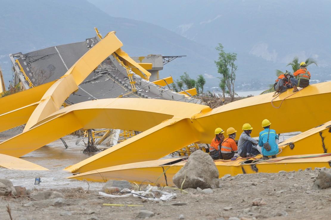 Pekerja memotong besi Jembatan Kuning yang ambruk diterjang tsunami di Palu, Sulawesi Tengah.