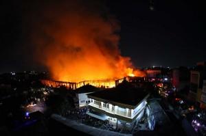 Kebakaran besar terjadi di dalam pasar bagian barat utara. Puluhan pedagang dibantu masyarakat sekitar terlihat menyelamatkan barang dagangan mereka.