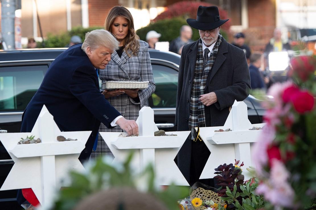 Melania Trump menaruh bunga dan presiden meletakkan batu kecil di atas foto masing-masing korban, sebagai doa belasungkawa sesuai tradisi Yahudi. Afp Photo/Saul Loeb