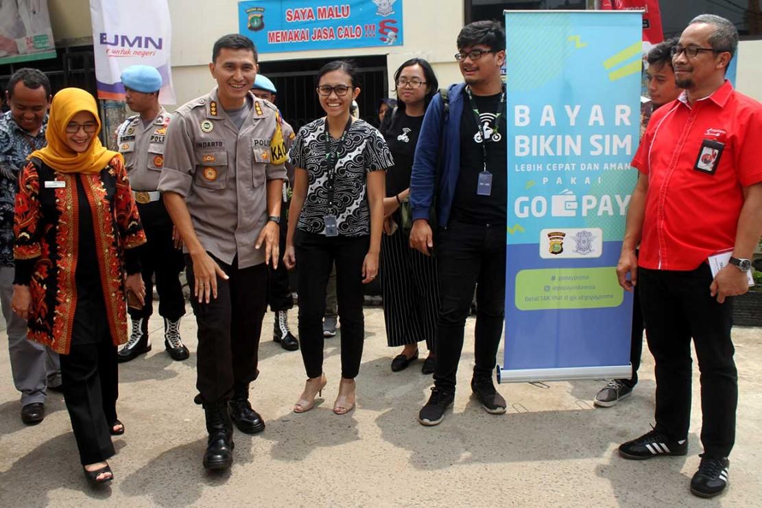 Kapolres Metro Bekasi Kota Kombes Indarto (kanan) mendengarkan penjelasan dari Government Relations and Policy GO-PAY Brigitta Ratih Aryanti (kedua kanan) saat peluncuran sistem pembayaran non tunai surat izin mengemudi (SIM), di Mapolres Metro Bekasi Kota, Bekasi, Jawa Barat, Jumat, 2 November 2018.