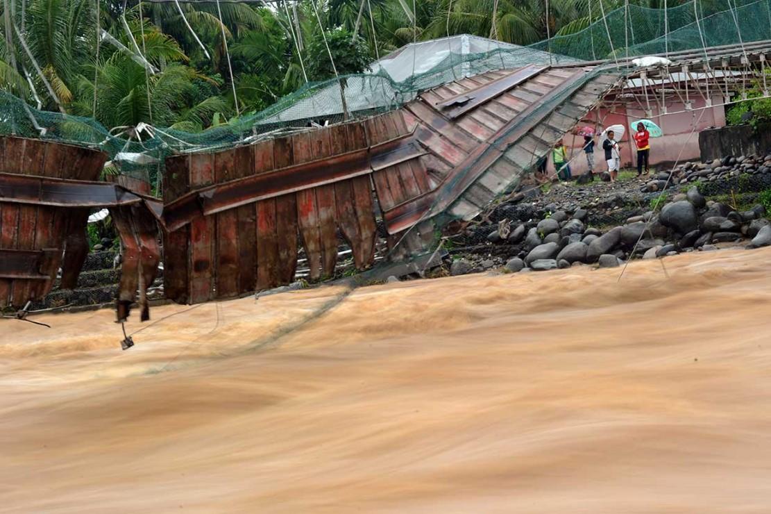 Warga melihat kondisi jembatan yang putus di Kelurahan Baringin, Lubuk Kilangan, Padang, Sumatera Barat, Jumat, 2 November 2018.