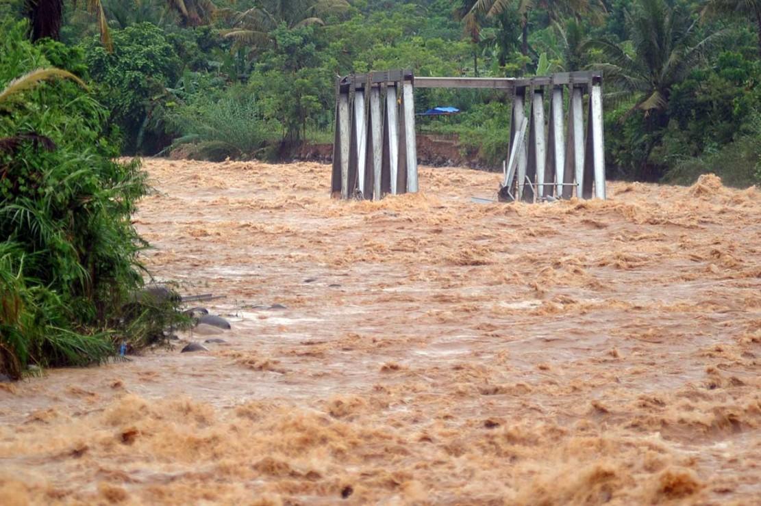 Rangka jembatan hanyut terbawa arus sungai yang meluap.