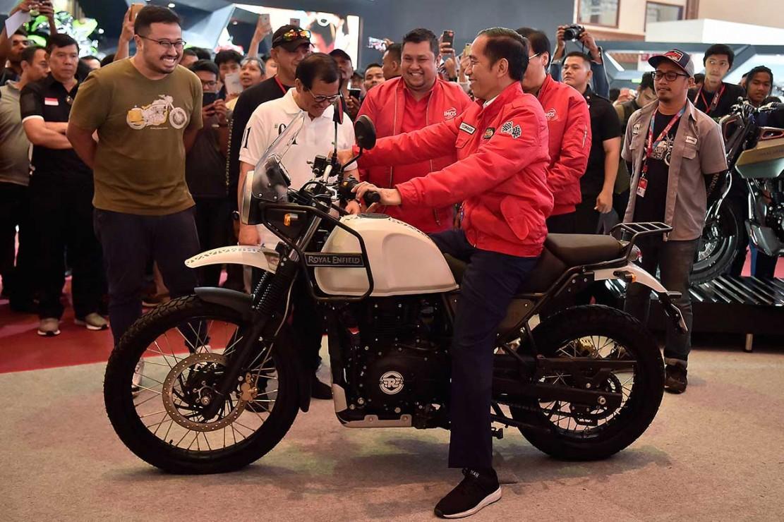 Mengenakan  jaket merah terang yang bagian belakangnya bertuliskan 'Bulls Syndicate, Motorcycle Worshiper' dengan huruf putih, Jokowi mencoba motor Royal Enfield berbadan putih dengan jok hitam.