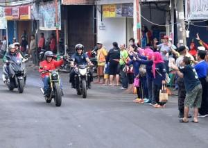 Membalas sapaan warga yang kaget mengetahui bahwa Presiden Jokowi sedang melintas dengan bersepeda motor.