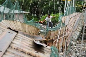 Warga melewati jembatan yang rusak di Kelurahan Baringin, Lubuk Kilangan, Padang, Sumatera Barat.
