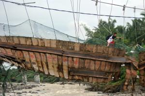 Seorang pelajar melewati jembatan yang rusak di Kelurahan Baringin, Lubuk Kilangan, Padang, Sumatera Barat.