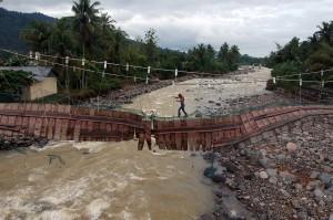 Jembatan darurat tersebut rusak akibat terjangan luapan sungai, namun warga nekat menggunakan jembatan itu untuk aktivitas sehari-hari.