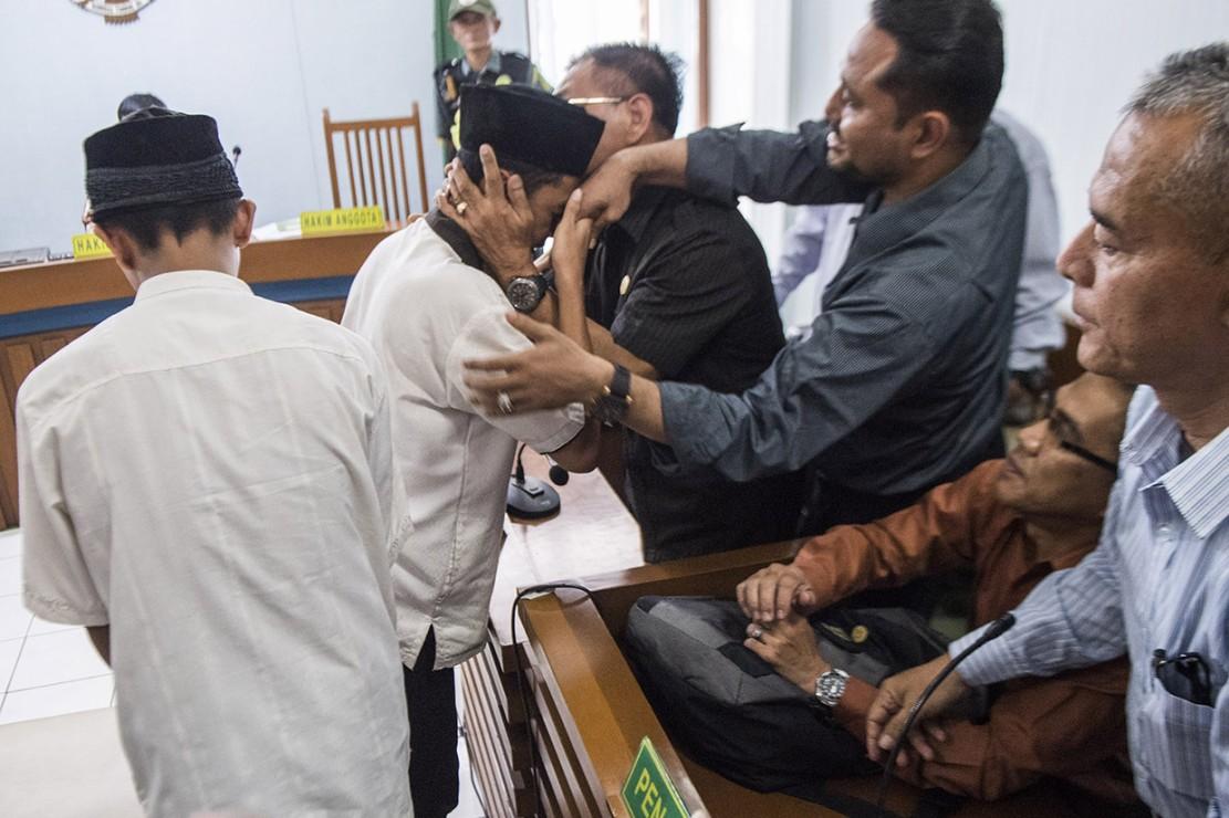 Dua terdakwa pengeroyokan Haringga Sirla yang berinisial AP (kiri) dan NSF (kedua kiri) memeluk pendamping seusai mengikuti sidang pembacaan putusan di Pengadilan Negeri Bandung, Jawa Barat.