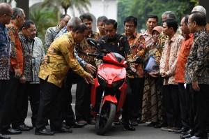 Presiden Joko Widodo (tengah) mendengarkan penjelasan dari Menristekdikti M Nasir (kelima kiri) sebelum menjajal motor listrik buatan dalam negeri 'Gesits' seusai melakukan audiensi dengan pihak-pihak yang terlibat proses produksi di halaman tengah Istana Kepresidenan, Jakarta.