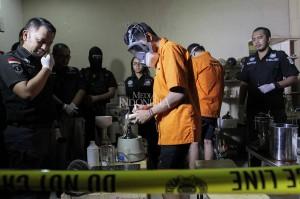 Tersangka kasus pembuatan dan pengedaran narkotika jenis liquid vape menunjukkan cara meracik narkoba liquid vape di ruang laboratorium di kompleks perumahan kawasan Kelapa Gading, Jakarta.