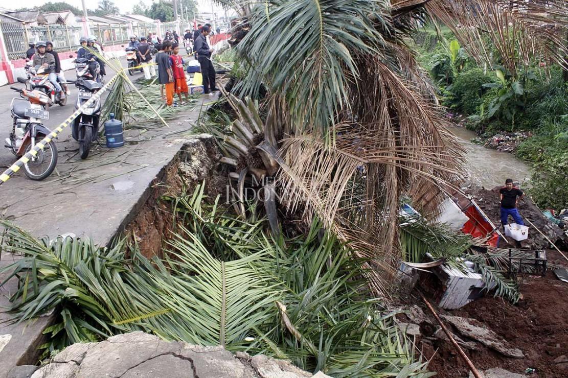 Warga melihat tanah longsor yang terjadi di Jalan Raya Citayam depan Perumahan Permata Depok, Kecamatan Cipayung, Depok, Jawa Barat, Jumat, 9 November 2018.