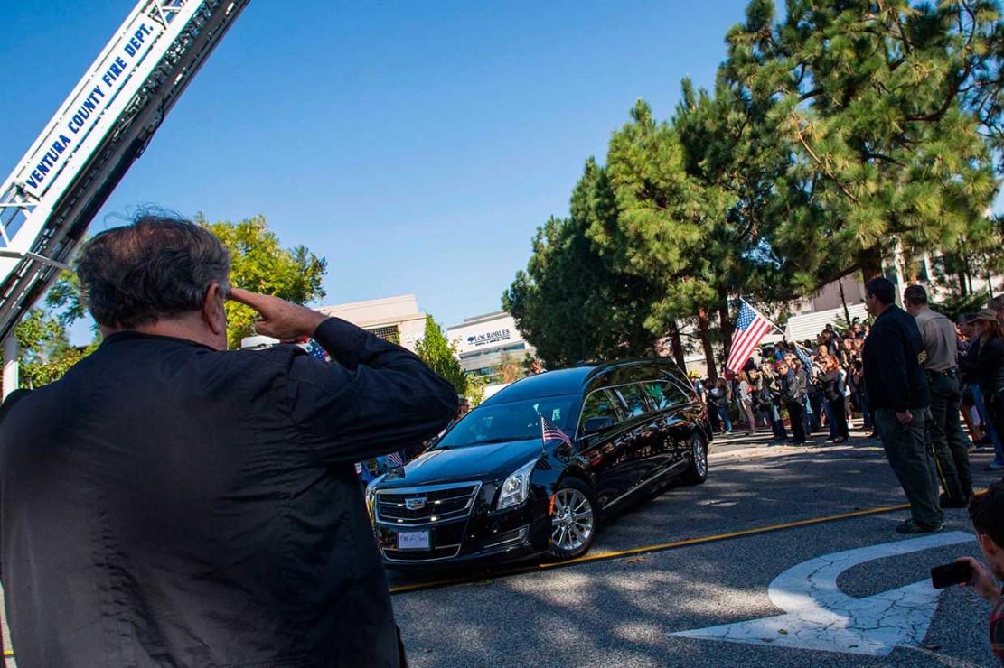 Warga memberi penghormatan saat iring-iringan mobil jenazah yang membawa mendiang Sheriff Ventura County Geoff Dean keluar dari sebuah rumah sakit di California. Geoff Dean merupakan salah satu korban tewas dalam penembakan di bar California.