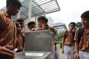 Pelajar mencoba fasilitas dispenser air siap minum yang tersedia di halaman Museum Nasional, Jakarta, Jumat, 9 November.
